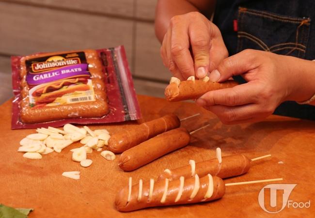 (2) 在香腸上斜切出坑紋(不要切斷),將蒜片插在坑紋內。